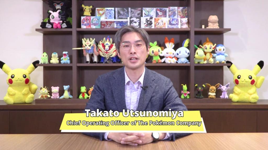 Takato Utsunomiya sitting at a desk in front of many Pokemon items.