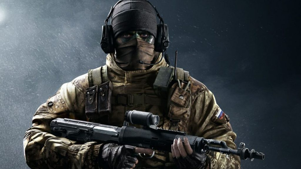 A picture of Glaz, an operator in Rainbow Six: Siege. He is wearing a beanie and a bandanna which covers his face along with green camouflage paint around his eyes. He is holding his iconic sniper rifle.